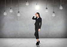 Femme d'affaires dans la chambre avec les ampoules accrochantes Photo libre de droits