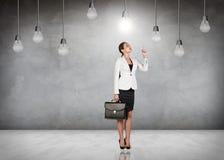 Femme d'affaires dans la chambre avec les ampoules accrochantes Photographie stock libre de droits