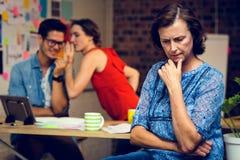 Femme d'affaires dans la pensée profonde et collègues chuchotant à l'arrière-plan photographie stock libre de droits