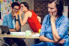 Femme d'affaires dans la pensée profonde et collègues chuchotant à l'arrière-plan image stock