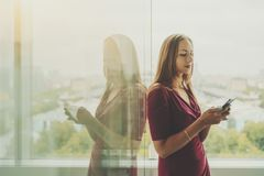 Femme d'affaires dans la robe rouge avec le téléphone portable près de la fenêtre Image libre de droits