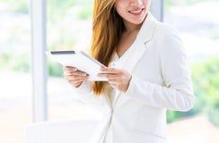 Femme d'affaires dans le blanc utilisant le comprimé dans le bureau photos stock