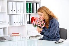 Femme d'affaires dans le bureau avec le grand bouquet des fleurs photo stock