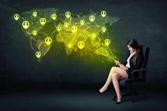 Femme d'affaires dans le bureau avec le comprimé et la carte sociale du monde de réseau Images stock
