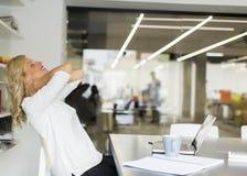 Femme d'affaires dans le bureau faisant une pause et faisant un exercice de cou images stock