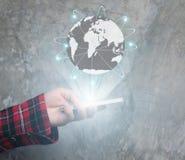 Femme d'affaires dans le bureau foncé utilisant l'interface tactile numérique du monde avec la main Images libres de droits