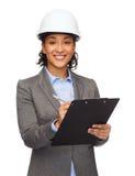 Femme d'affaires dans le casque blanc avec le presse-papiers Photographie stock