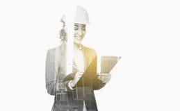 Femme d'affaires dans le casque de bâtiment avec le presse-papiers Photo stock