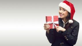 Femme d'affaires dans le chapeau de Santa tenant le cadeau Photographie stock