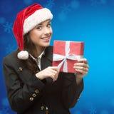 Femme d'affaires dans le chapeau de Santa tenant le cadeau Photographie stock libre de droits