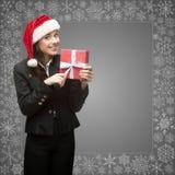 Femme d'affaires dans le chapeau de Santa tenant le cadeau Images stock