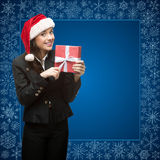 Femme d'affaires dans le chapeau de Santa tenant le cadeau Photo libre de droits