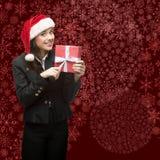 Femme d'affaires dans le chapeau de Santa tenant le cadeau Image stock