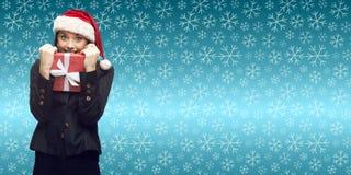 Femme d'affaires dans le chapeau de Santa tenant le cadeau Photos stock