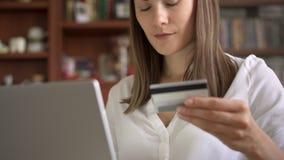 Femme d'affaires dans le chemisier blanc se reposant sur le sofa dans le salon achetant en ligne avec la carte de crédit sur l'or banque de vidéos