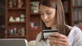 Femme d'affaires dans le chemisier blanc se reposant sur le sofa dans le salon achetant en ligne avec la carte de crédit sur l'or clips vidéos