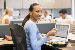 Femme d'affaires dans le compartiment avec l'ordinateur portatif mangeant de la salade photographie stock