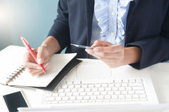 Femme d'affaires dans le costume foncé tenant la carte de crédit, utilisant l'ordinateur portable Images libres de droits