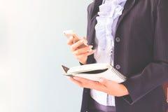 Femme d'affaires dans le costume foncé tenant le téléphone portable et le carnet, concept d'affaires Photo libre de droits