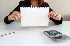 Femme d'affaires dans le costume noir montrant la page vide du bloc-notes sur d Photographie stock libre de droits