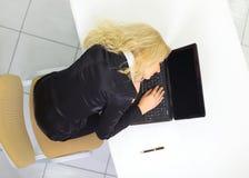 Femme d'affaires dans le procès noir dormant sur l'ordinateur portatif Image libre de droits