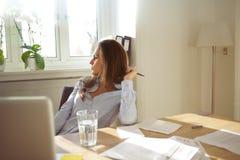 Femme d'affaires dans le siège social regardant loin pensant Images libres de droits