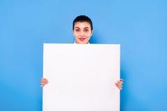 Femme d'affaires dans le tenue de soirée avec le panneau blanc sur le backgroun bleu Photo libre de droits
