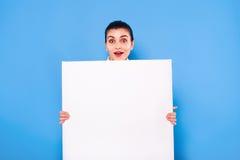 Femme d'affaires dans le tenue de soirée avec le panneau blanc sur le backgroun bleu Photographie stock libre de droits
