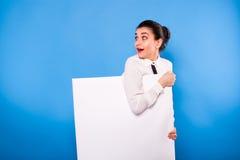 Femme d'affaires dans le tenue de soirée avec le panneau blanc sur le backgroun bleu Photos libres de droits