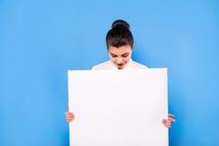 Femme d'affaires dans le tenue de soirée avec le panneau blanc sur le backgroun bleu Photographie stock