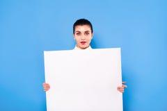 Femme d'affaires dans le tenue de soirée avec le panneau blanc sur le backgroun bleu Images libres de droits