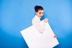 Femme d'affaires dans le tenue de soirée avec le panneau blanc sur le backgroun bleu Image libre de droits
