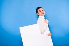 Femme d'affaires dans le tenue de soirée avec le panneau blanc sur le backgroun bleu Photo stock