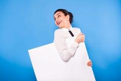 Femme d'affaires dans le tenue de soirée avec le panneau blanc sur le backgroun bleu Images stock