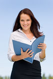 Femme d'affaires dans les dépliants de sourire de prise de nature ensoleillée Photographie stock libre de droits