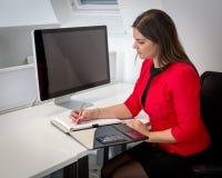 Femme d'affaires dans les notes rouges d'écriture de manteau de taille Photo stock