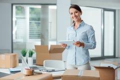 Femme d'affaires dans son nouveau bureau utilisant un comprimé Photos stock