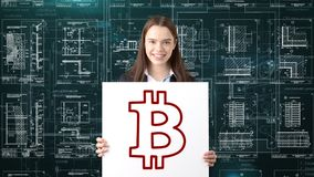 Femme d'affaires de Bauty se tenant dans le costume avec le logo de Bitcoin pour illustrer l'utilisation du bitcoin pour le comme photo stock