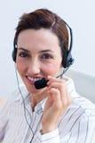 Femme d'affaires de brune de portrait souriant utilisant l'écouteur Images stock