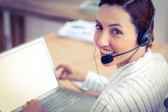 Femme d'affaires de brune de portrait souriant utilisant l'ordinateur portable et l'écouteur Photos stock
