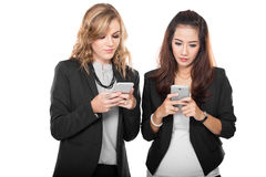 Femme d'affaires de deux jeunes regardant leur téléphone, d'isolement Photographie stock