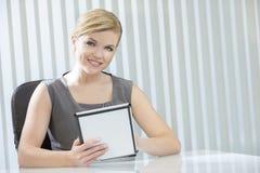Femme d'affaires de femme sur l'ordinateur de tablette dans le bureau Image libre de droits