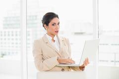 Femme d'affaires de froncement de sourcils se tenant derrière sa chaise tenant l'ordinateur portable Photo stock
