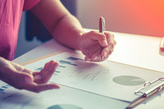 Femme d'affaires de l'Asie analysant des diagrammes d'investissement sur le bureau Photographie stock