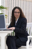 Femme d'affaires de Latina avec des glaces à l'ordinateur portatif photos stock