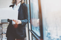 Femme d'affaires de photo portant le costume moderne et tenant des papiers dans des mains Bureau de grenier de l'espace ouvert Fo Photo stock