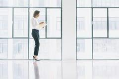 Femme d'affaires de photo portant le costume moderne, regardant le téléphone portable et tenant des papiers dans des mains Bureau Photos libres de droits
