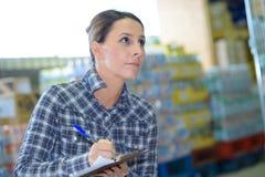 Femme d'affaires de portrait faisant l'inventaire dans l'entrepôt images libres de droits