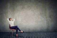 Femme d'affaires de refroidissement s'asseyant sur la chaise images libres de droits