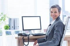 Femme d'affaires de sourire à l'aide de l'ordinateur image libre de droits